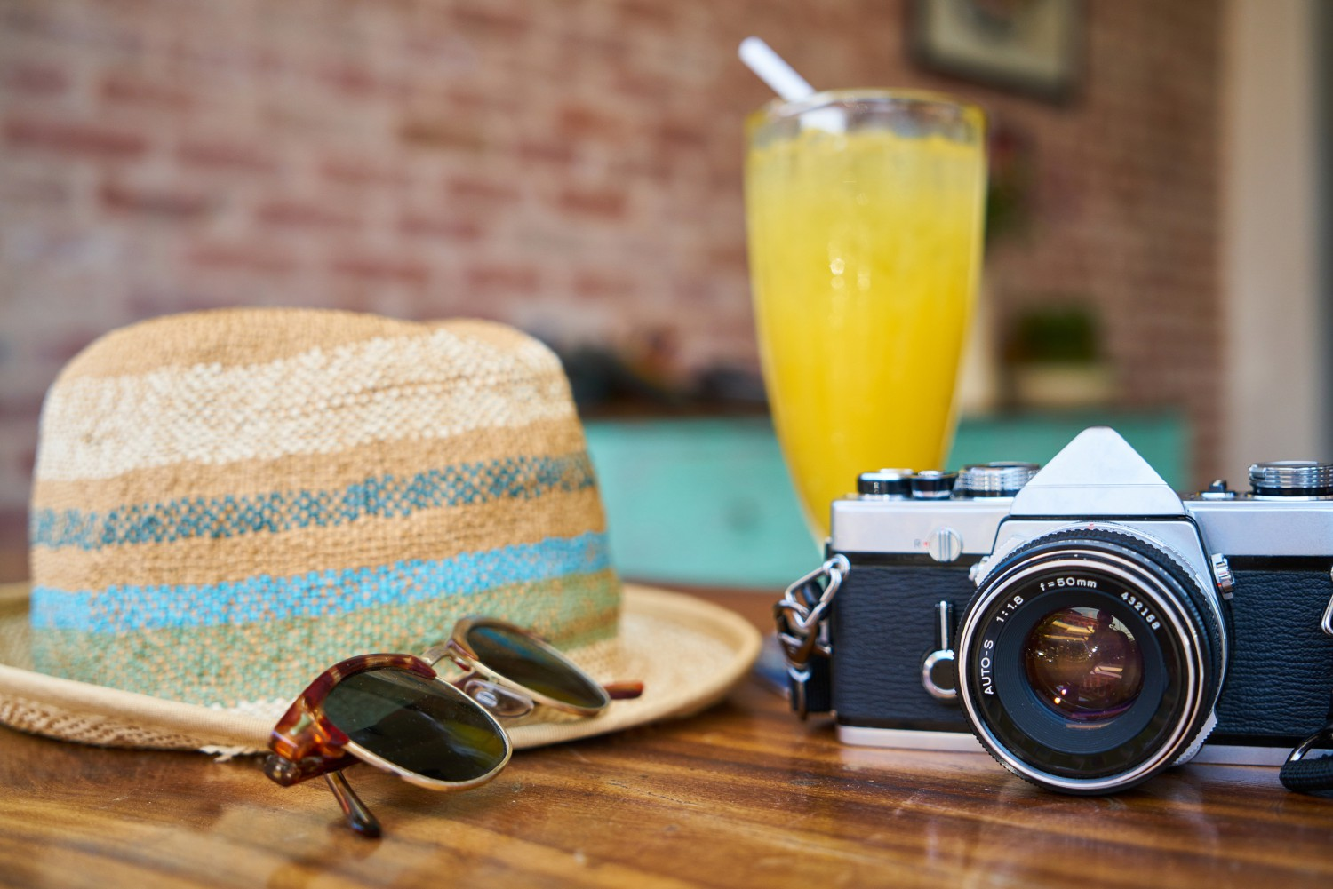 A hat, sunglasses, a glass of juice, and a camera on a table