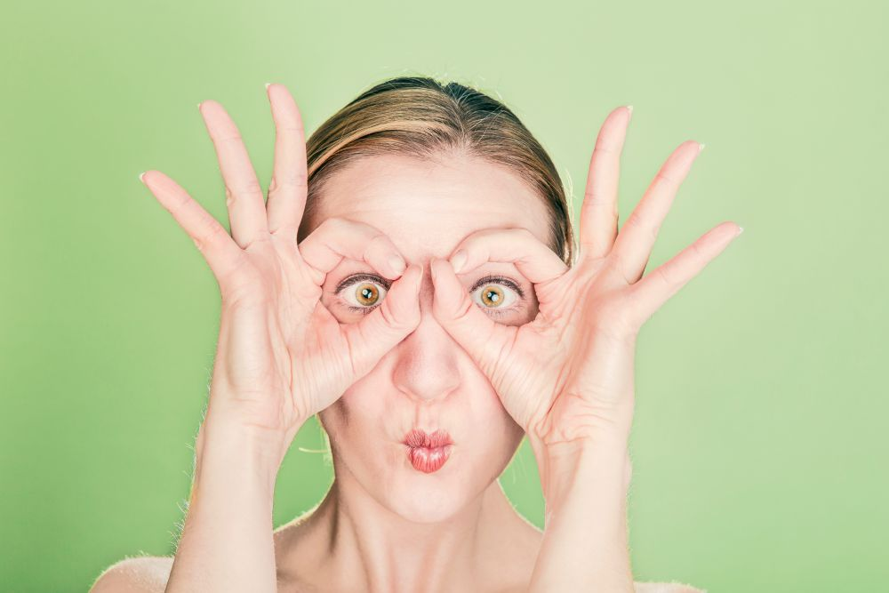 A woman making a glasses face with her hands and eyes